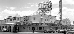 Daytime exterior photo of El Cortez with 1950s automobiles driving by
